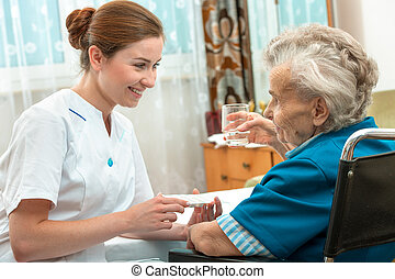 Taking medicine - female nurse giving senior woman medical...