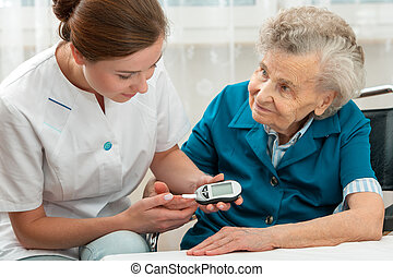 Measuring blood glucose level - Female nurse measuring blood...