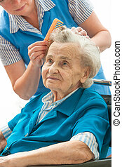 Hair care - Caregiver dressing the hair of a senior woman...