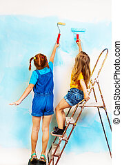 Two girls stand on a ledge and paint wall