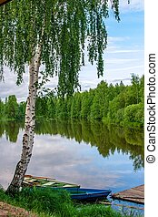 two old boats on the river under the birch
