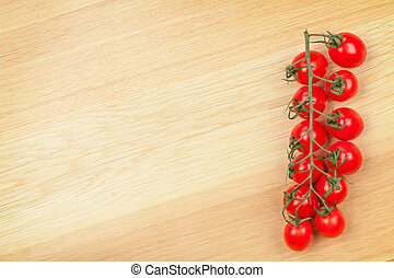 Cherry tomatoes on wooden table background with copy space