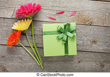 Three colorful gerbera flowers with gift box on wooden table