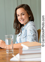 Smiling teenage girl student at home