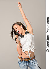Teenage girl dancing singing with microphone - Teenage girl...
