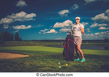 Young cheerful woman with bag and bottle of water on a golf...