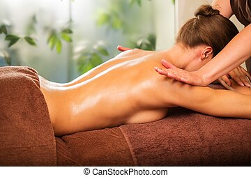 Young woman having massage in a spa salon