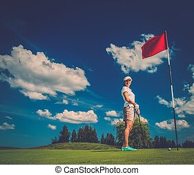 Young woman near hole with red flag on a golf club field