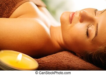Beautiful young woman relaxing in a spa salon