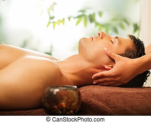 Handsome man having face massage in spa salon