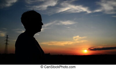 Woman smoking cigarette in sunset - Silhouette of young...