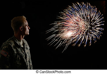 Freedom Rings - A soldier stands watching fireworks blow in...