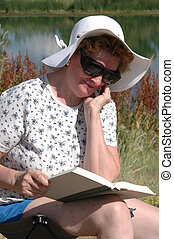 Lakeside Read - A woman in a chair by the lake reading a...