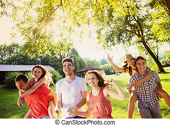 Friends having fun in park - Group of five teenage friends...