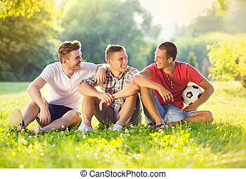Leisure time in park - Three happy friends spending free...