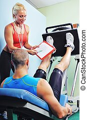 Athlete man in gym with personal fitness trainer