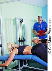 Woman in gym exercising with personal fitness trainer