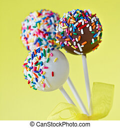 Colorful cake pops - Three cake pops against a yellow...