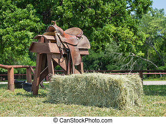 Leather horse saddle and a hay bale - Leather horse saddle...