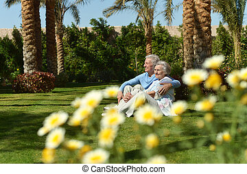 Old couple in garden - Loving elder couple sitting on a...