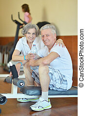 Portrait Of A Senior Couple Exercising in Gym, drinking...