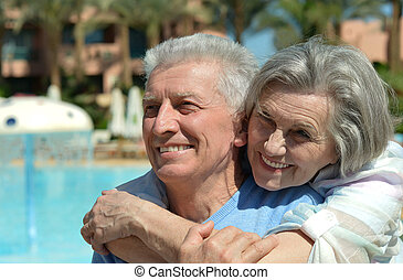 Senior loving couple - Senior couple standing by pool at the...