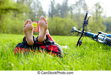 Cyclist on a halt reads lying in fresh green grass barefoot...