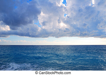 Heavy clouds and vast deep blue sea waters