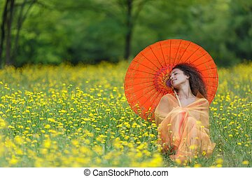 Beautiful elegant woman with an orange parasol draped in a...