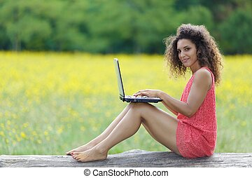 Pretty barefoot woman working on a laptop - Pretty barefoot...