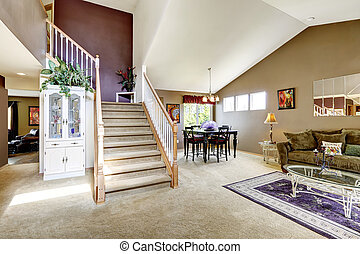 House interior with open floor plan. Living room with staircase