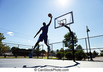 Basketball Player Silhouette - A young basketball player...