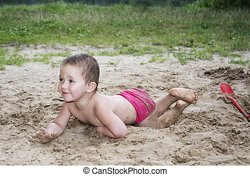Little funny girl lying on the sand near the lake in summer and