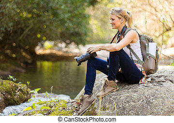 young photographer resting in mountain valley - young female...