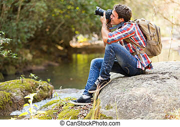 photographer photographing in mountain valley - young...