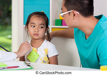 Asian dad with sick daughter at doctors office