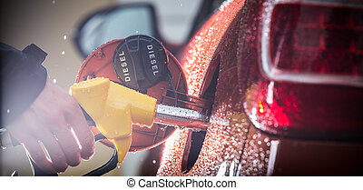 Hand refilling the car with fuel. - Hand refilling the car...