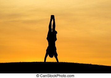 Doing a hand stand at sunset. - A young boy does a hand...