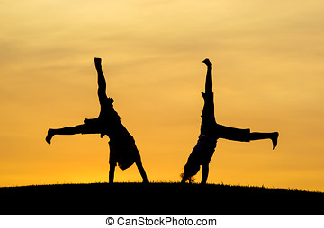 Brother and sister doing cartwheels. - A boy and girl are...