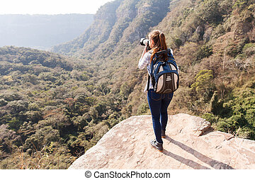 young woman taking photos on top of mountain