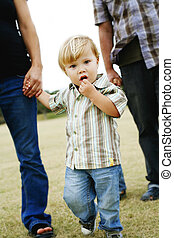 Child walking with parents in a park. - A small boy walking...