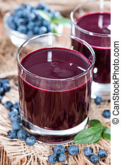 Glass with Blueberry Juice and fresh fruits close-up shot