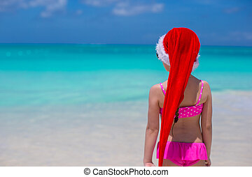 Back view of cute girl in red hat santa claus on the beach -...