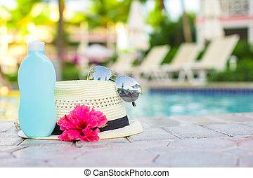 Suncream, hat, sunglasses, flower and tower near swimming...