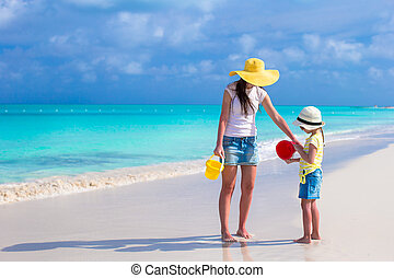 Little cute girl and young mother playing at tropical beach