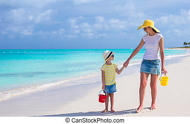 Little adorable girl and young mother playing at tropical beach