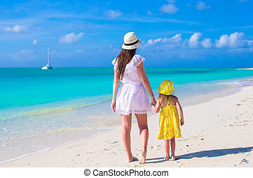 Mother and daughter walking along a tropical beach - Young...