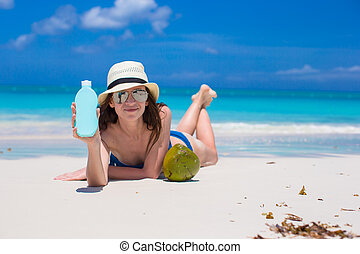 Beautiful young woman holding a suncream lying on tropical...