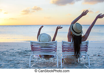 Little girl and mother sitting on beach chairs at sunset