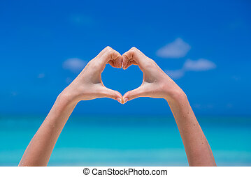 Close up of heart made by female hands background the turquoise ocean